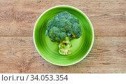 Green broccoli inflorescence on a green plate on a wooden tabletop. Стоковое фото, фотограф Евгений Харитонов / Фотобанк Лори
