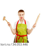 young and pretty housewife with a rolling pin and meat hammer in her hands. Стоковое фото, фотограф Nataliia Zhekova / Фотобанк Лори