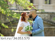 Купить «Just married loving hipster couple in wedding dress and suit in the park. Happy bride and groom walking running and dancing.», фото № 34053570, снято 5 октября 2018 г. (c) Nataliia Zhekova / Фотобанк Лори