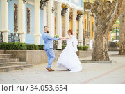 Купить «Just married loving hipster couple in wedding dress and suit in the park. Happy bride and groom walking running and dancing. Romantic Married young family.», фото № 34053654, снято 5 октября 2018 г. (c) Nataliia Zhekova / Фотобанк Лори