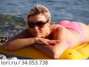 Happy woman in bikini lying on air bed on the beach. Стоковое фото, фотограф Константин Сиятский / Фотобанк Лори