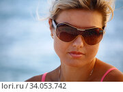 Close-up portrait Beautiful caucasian woman having fun on summer wearing sunglasses on blue sea background. Model looking at camera. Стоковое фото, фотограф Константин Сиятский / Фотобанк Лори