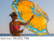 Smiling woman in sunglasses and bikini at the seaside under an umbrella in the summer. Стоковое фото, фотограф Константин Сиятский / Фотобанк Лори