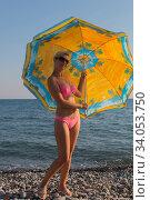 Smiling woman in sunglasses bikini at the seaside under an umbrella in the summer. Стоковое фото, фотограф Константин Сиятский / Фотобанк Лори