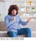 Купить «Funny man singing songs in karaoke at home», фото № 34054350, снято 29 марта 2017 г. (c) Elnur / Фотобанк Лори