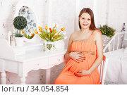 Pregnant woman sitting near a mirror in interior with Shabby chic decor. Стоковое фото, фотограф Nataliia Zhekova / Фотобанк Лори