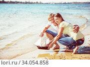 Купить «happy young couple enjoying picnic on the beach and have good time on summer», фото № 34054858, снято 6 сентября 2014 г. (c) Nataliia Zhekova / Фотобанк Лори