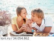 Купить «happy young couple enjoying picnic on the beach and have good time on summer», фото № 34054862, снято 6 сентября 2014 г. (c) Nataliia Zhekova / Фотобанк Лори