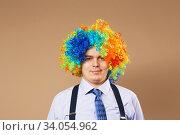 Купить «Smiling businessman with large colorful wig», фото № 34054962, снято 28 февраля 2016 г. (c) Nataliia Zhekova / Фотобанк Лори