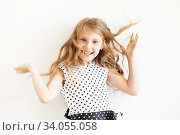 Lovely frisky little girl in a polka-dot dress against a white background. Стоковое фото, фотограф Nataliia Zhekova / Фотобанк Лори