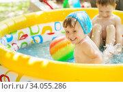 Kids splashing water and having fun in Swim Pool. Стоковое фото, фотограф Nataliia Zhekova / Фотобанк Лори