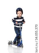 Купить «Little boy in protection helmet and in the knee and arm ruffles riding his scooter», фото № 34055370, снято 18 марта 2015 г. (c) Nataliia Zhekova / Фотобанк Лори