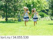 Купить «Две сестренке бегут по зеленому газону в парке», фото № 34055530, снято 16 июня 2020 г. (c) Иванов Алексей / Фотобанк Лори