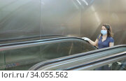 Young woman wearing medical mask and rubber gloves coming out of metro station, moving up on escalator. Necessary precautions during Covid 19 virus pandemic. Стоковое видео, видеограф Яков Филимонов / Фотобанк Лори