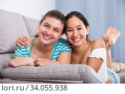 Cheerful teens girls laughing on couch. Стоковое фото, фотограф Яков Филимонов / Фотобанк Лори