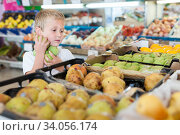 kid holds fruit at vegetable section. Стоковое фото, фотограф Яков Филимонов / Фотобанк Лори