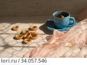Мелкие баранки и чашка с чаем на деревянном столе в солнечном свете около окна. Стоковое фото, фотограф Наталья Гармашева / Фотобанк Лори