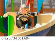 Cute little blond toddler girl sliding down the children's slide at playground. Стоковое фото, фотограф Zoonar.com/Serghei Starus / easy Fotostock / Фотобанк Лори