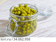 Home canning of summer legume crop, vegetable vegetarian diet healthy food, natural green peas marinated in a glass jar close-up on the table. Стоковое фото, фотограф Светлана Евграфова / Фотобанк Лори