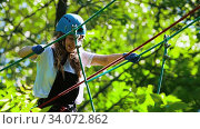 Купить «Rope adventure - woman carefully walks upwards on the suspension rope bridge», видеоролик № 34072862, снято 7 июля 2020 г. (c) Константин Шишкин / Фотобанк Лори