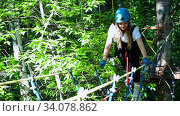 Купить «Extreme rope adventure - smiling woman walking on the suspension rope bridge in the park», видеоролик № 34078862, снято 7 июля 2020 г. (c) Константин Шишкин / Фотобанк Лори