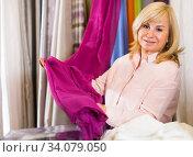 Купить «Mature woman customer choosing color curtains», фото № 34079050, снято 17 января 2018 г. (c) Яков Филимонов / Фотобанк Лори