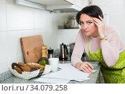 Sad middle aged housewife looking through bills. Стоковое фото, фотограф Яков Филимонов / Фотобанк Лори