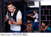 Portrait of excited guy with laser pistol playing laser tag in arena. Стоковое фото, фотограф Яков Филимонов / Фотобанк Лори