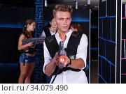 Купить «guy holding laser pistol playing laser tag game», фото № 34079490, снято 27 августа 2018 г. (c) Яков Филимонов / Фотобанк Лори