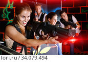 Portrait of exciting girl with laser pistol playing laser tag in. Стоковое фото, фотограф Яков Филимонов / Фотобанк Лори