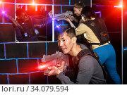 Chinese man during lasertag game in dark room. Стоковое фото, фотограф Яков Филимонов / Фотобанк Лори