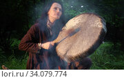 Shaman woman playing on shaman frame drum in the nature. Стоковое видео, видеограф Алексей Кузнецов / Фотобанк Лори
