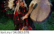 Female shaman in native American Indian headdress performs a ritual with a tambourine at night in the forest by the fire. Стоковое видео, видеограф Алексей Кузнецов / Фотобанк Лори