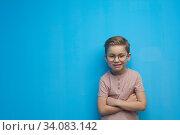 Купить «Little cute boy with glasses posing on a blue background», фото № 34083142, снято 10 марта 2019 г. (c) Pavel Biryukov / Фотобанк Лори