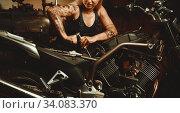 Blond woman mechanic repairing a motorcycle in a workshop. Стоковое фото, фотограф Alexander Tihonovs / Фотобанк Лори