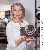 Woman offering to buy fashionable rose quartz necklace in the shop of jewelry. Стоковое фото, фотограф Яков Филимонов / Фотобанк Лори