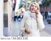 Smiling mature woman talking on phone and walking. Стоковое фото, фотограф Яков Филимонов / Фотобанк Лори