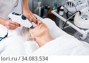 Aged woman making beauty procedures for face. Стоковое фото, фотограф Яков Филимонов / Фотобанк Лори