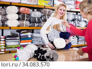 Shop assistant is offering coverlets to aged woman. Стоковое фото, фотограф Яков Филимонов / Фотобанк Лори