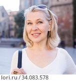 Купить «Cheerful mature female is walking in white blouse on the street outdoor», фото № 34083578, снято 11 марта 2020 г. (c) Яков Филимонов / Фотобанк Лори