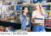 Купить «Cheerful girl picking textbooks with telephone», фото № 34083654, снято 9 мая 2017 г. (c) Яков Филимонов / Фотобанк Лори