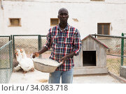 Купить «Male farmer with bird feed standing near enclosure gooses», фото № 34083718, снято 6 августа 2019 г. (c) Яков Филимонов / Фотобанк Лори