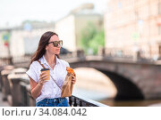 Woman with a croissant and coffee outdoors on the promenade. Стоковое фото, фотограф Дмитрий Травников / Фотобанк Лори
