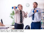 Купить «Two employees doing physical exercises at workplace», фото № 34087562, снято 7 октября 2019 г. (c) Elnur / Фотобанк Лори