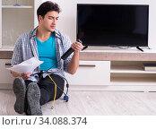 Купить «Man trying to fix broken tv», фото № 34088374, снято 9 марта 2018 г. (c) Elnur / Фотобанк Лори
