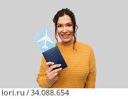 Купить «smiling young woman with passport and air ticket», фото № 34088654, снято 20 марта 2020 г. (c) Syda Productions / Фотобанк Лори