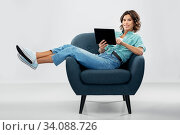 happy woman with tablet pc sitting in armchair. Стоковое фото, фотограф Syda Productions / Фотобанк Лори