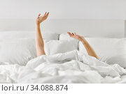 hands of woman lying in bed and stretching. Стоковое фото, фотограф Syda Productions / Фотобанк Лори