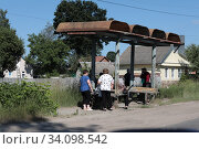 Купить «Люди на ржавой обшарпанной остановке общественного транспорта  остановке, окраина города Клинцы», эксклюзивное фото № 34098542, снято 24 июня 2020 г. (c) Дмитрий Неумоин / Фотобанк Лори