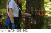 Купить «Extreme rope adventure - instructor explaining to a woman how to use the insurance hook», видеоролик № 34098842, снято 7 июля 2020 г. (c) Константин Шишкин / Фотобанк Лори